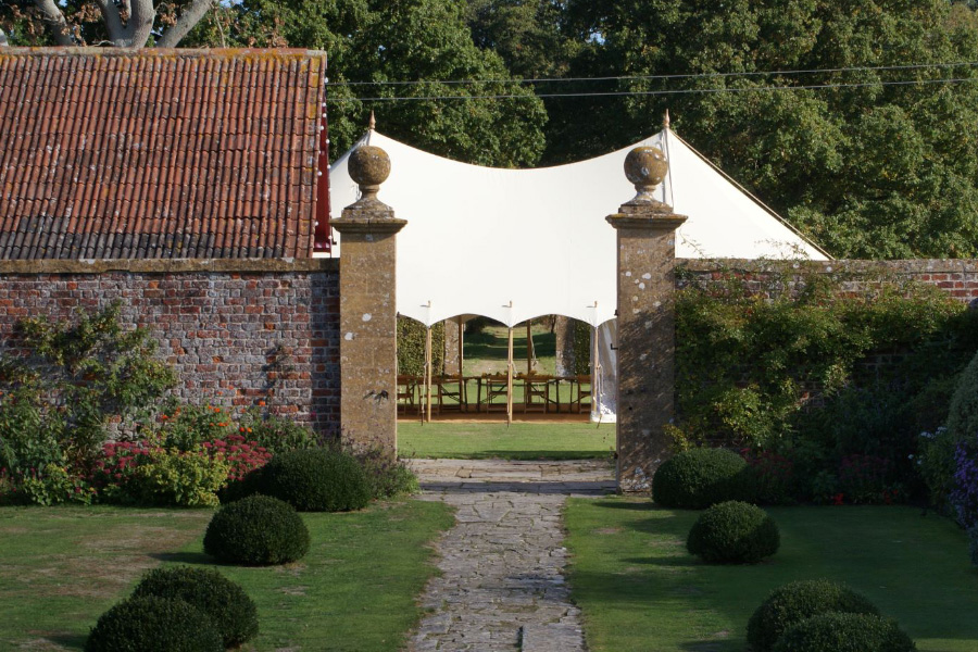 Traditional Pole Marquee in a walled garden setting.